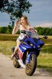 Mujer joven con una velocidad de la motocicleta Imagenes de archivo