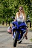 Mujer joven con una velocidad de la motocicleta Imágenes de archivo libres de regalías