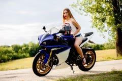 Mujer joven con una velocidad de la motocicleta Imagen de archivo libre de regalías