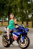 Mujer joven con una velocidad de la motocicleta Fotografía de archivo libre de regalías