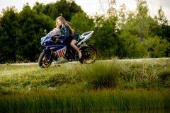 Mujer joven con una velocidad de la motocicleta Foto de archivo