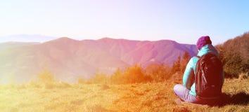 Mujer joven con viaje de la mochila en montañas Imagenes de archivo