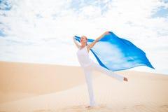 Mujer joven con volar la bufanda azul Foto de archivo