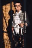 Mujer joven concentrada que se sienta en el granero que lleva a cabo el seddle Fotografía de archivo
