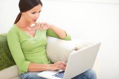 Mujer joven concentrada que trabaja en el ordenador portátil Fotos de archivo libres de regalías