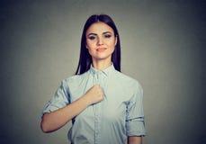 Mujer joven confiada aislada en fondo gris de la pared imagen de archivo