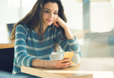 Mujer joven confiada en el café usando un smartphone Fotos de archivo