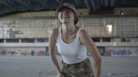 Mujer joven confiada en el entrenamiento del uniforme militar en el edificio abandonado sucio polvoriento Muchacha delgada que co almacen de video