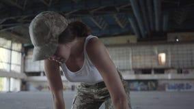 Mujer joven confiada en el entrenamiento del uniforme militar en el edificio abandonado sucio polvoriento Muchacha delgada que co metrajes