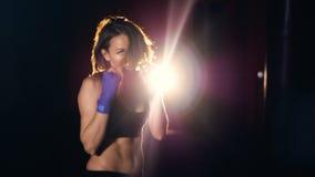 Mujer joven confiada en los guantes de boxeo que encajonan mirando la cámara almacen de video