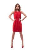 Mujer joven confiada en vestido rojo con las manos en caderas foto de archivo