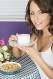 Mujer joven confiada feliz atractiva que come café de consumición del desayuno Imagen de archivo