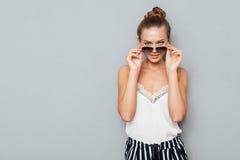 Mujer joven confiada que mira la cámara a través de las gafas de sol Foto de archivo libre de regalías