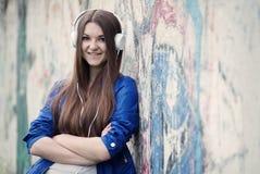 Mujer joven confiada sonriente que escucha la música Imagen de archivo libre de regalías