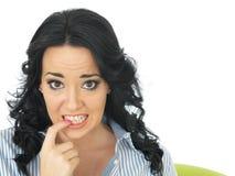 Mujer joven confusa ansiosa preocupante que muerde su clavo Imágenes de archivo libres de regalías