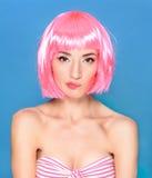 Mujer joven confusa con el pelo rosado en un fondo azul Imagen de archivo