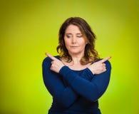 Mujer joven confusa que señala con los fingeres en dos diversas direcciones Imagen de archivo libre de regalías