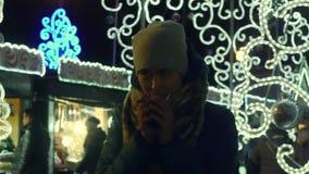 Mujer joven congelada que intenta guardar té caliente caliente, de consumición en la feria de la Navidad metrajes