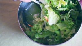 Mujer joven consciente de la salud que lanza una ensalada verde orgánica sabrosa almacen de video