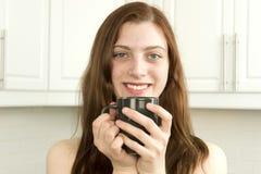Mujer joven contenta con la taza de té o de café Imagen de archivo