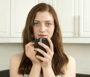 Mujer joven contenta con la taza de té o de café Imagen de archivo libre de regalías