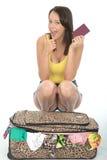 Mujer joven contenta emocionada feliz que se arrodilla detrás de una maleta que sostiene un pasaporte Fotografía de archivo