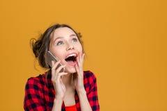 Mujer joven contenta sorprendida encantadora que habla en el teléfono celular Foto de archivo