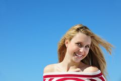 Mujer joven contra el cielo azul fotografía de archivo