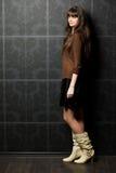 Mujer joven contra la pared con el modelo Imágenes de archivo libres de regalías