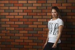 Mujer joven contra la pared de ladrillo Imagen de archivo libre de regalías