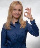 Mujer joven curiosa en la muestra azul casual de la AUTORIZACIÓN de la demostración de la camisa que mira derecho en cámara fotografía de archivo libre de regalías