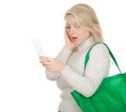 Mujer joven dada una sacudida eléctrica con el recibo Foto de archivo libre de regalías