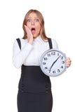 Mujer joven dada una sacudida eléctrica que sostiene el reloj Imagenes de archivo