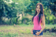Mujer joven de Asia que lleva el chaleco rosado en parque fotos de archivo