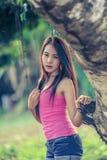 Mujer joven de Asia que lleva el chaleco rosado en parque imágenes de archivo libres de regalías