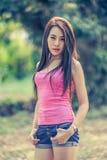 Mujer joven de Asia que lleva el chaleco rosado y vaqueros cortos fotos de archivo