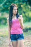 Mujer joven de Asia que lleva el chaleco rosado y vaqueros cortos imagenes de archivo