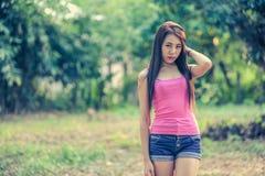 Mujer joven de Asia que lleva el chaleco rosado y vaqueros cortos fotografía de archivo