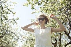 Mujer joven de baile en el jardín floreciente de la primavera Imágenes de archivo libres de regalías