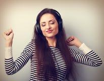 Mujer joven de baile que escucha la música de los auriculares con clo Foto de archivo libre de regalías