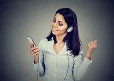Mujer joven de baile que escucha la música en auriculares y sostener el teléfono móvil en fondo gris oscuro fotos de archivo libres de regalías
