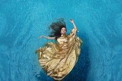 Mujer joven de Bbeautiful en el vestido del oro, vestido de noche que flota la flotación ingrávido elegante en el agua en la pisc fotos de archivo libres de regalías