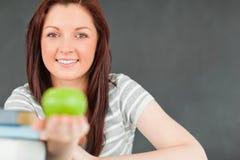 Mujer joven de Beautilful que muestra una manzana Imágenes de archivo libres de regalías