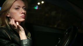 Mujer joven de Blondie que conduce un coche en noche almacen de video