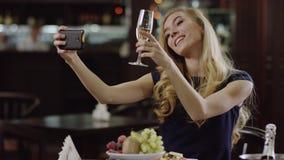 Mujer joven de Blondie que toma un selfie en un restaurante de lujo metrajes