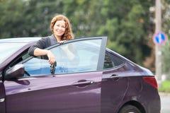 Mujer joven de Brunett cerca de propio coche con llaves Foto de archivo libre de regalías