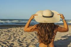 Mujer joven de detrás, sombrero del verano que lleva y vaqueros de los pantalones cortos Fotografía de archivo libre de regalías