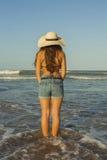 Mujer joven de detrás, sombrero del verano que lleva y vaqueros de los pantalones cortos en Imagen de archivo libre de regalías