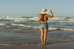 Mujer joven de detrás, sombrero del verano que lleva y vaqueros de los pantalones cortos en Imagenes de archivo
