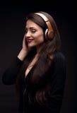 Mujer joven de goce hermosa del pelo largo que escucha la música adentro Imagen de archivo libre de regalías